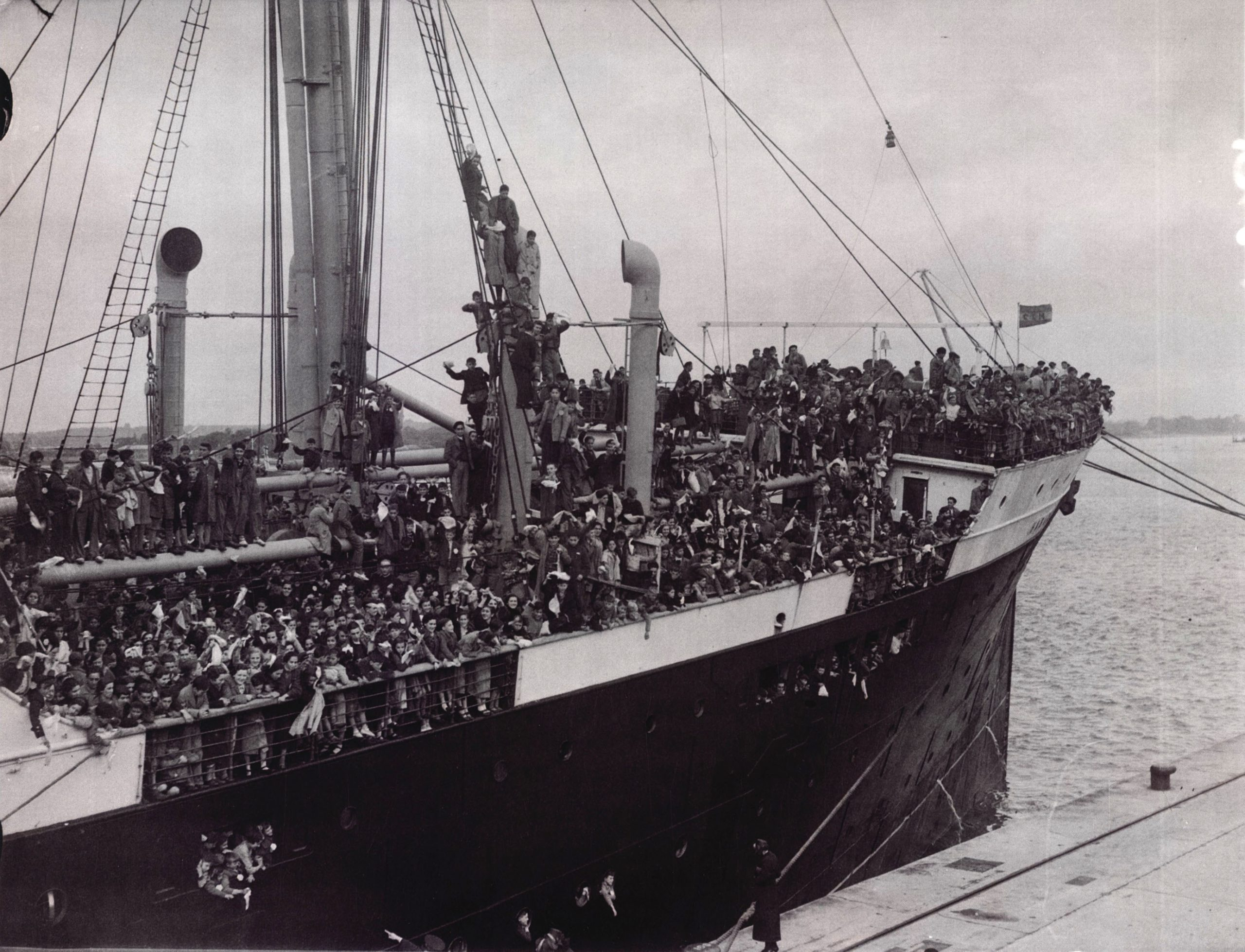 A photo of a ship carrying the child refugees. They fill the docks and some have climbed masts.